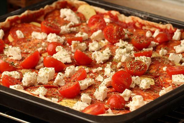 Pizza with sausages, potatoes and feta